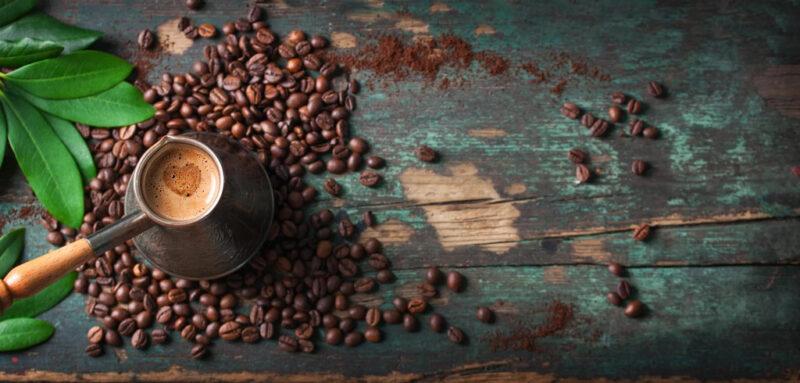Ein Kaffeekännchen aus der Vogelperspektive auf gerösteten Kaffeebohnen.