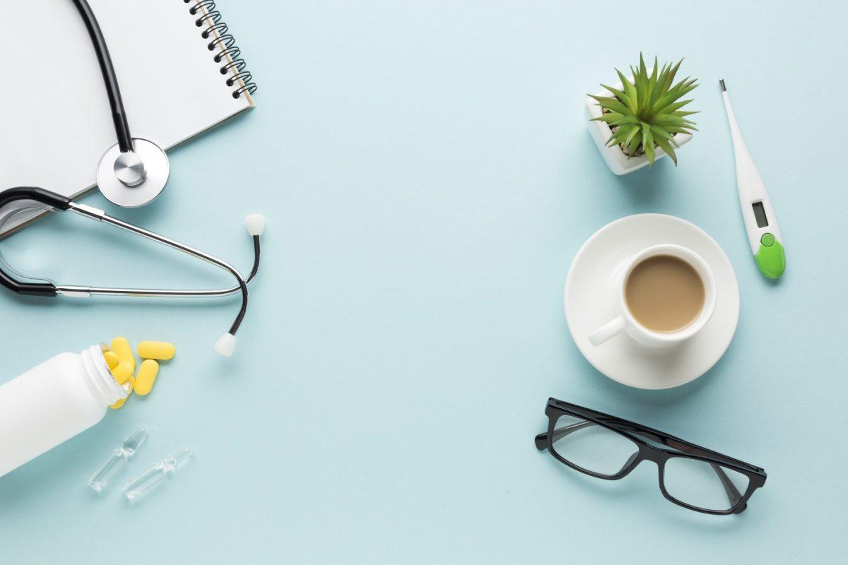 Kaffeetasse und Arztutentsilien auf hellblauem Tisch.