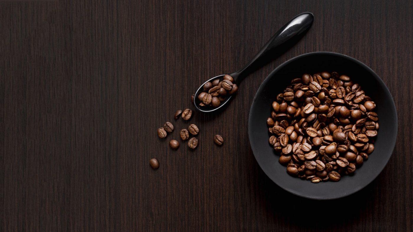 Geröstete Kaffeebohnen in schwarzer Schale und Löffel.