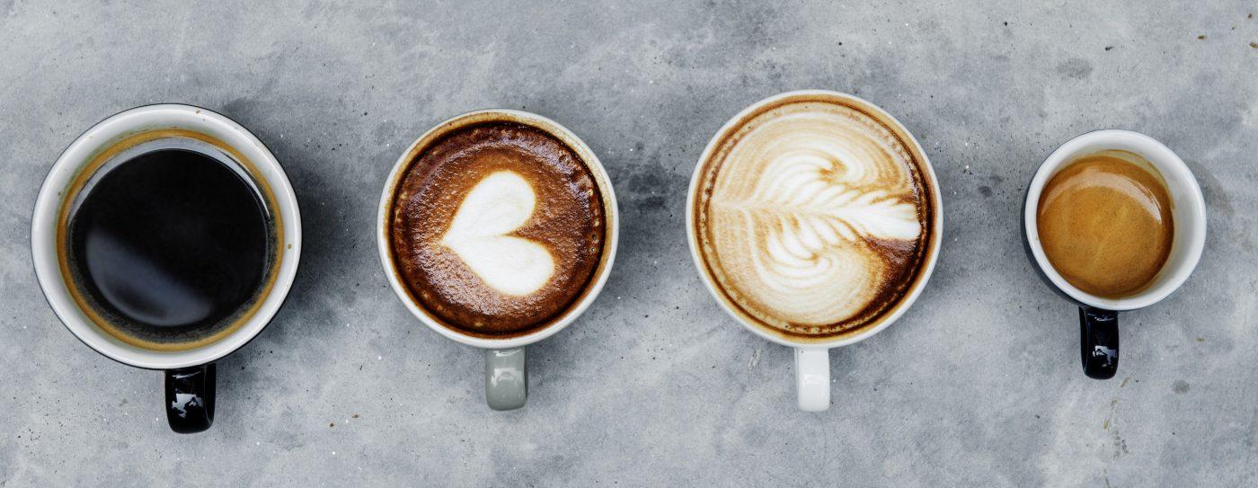 Verschiedene Zubereitungsarten von Kaffee in Tassen aneinandergereiht.